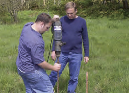 Jay Shaw, right, directs his son, Robert, in drilling the 2-foot holes necessary to place the black powder